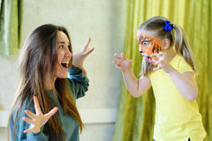 Adorable little girl painted like tiger playing with animator Stock Image