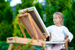 Adorable little girl painting a picture on easel outdoors Stock Photo