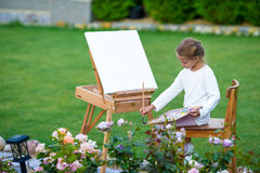 Adorable little girl painting a picture on easel outdoors. Little artist keen on her hobby. Stock Photo