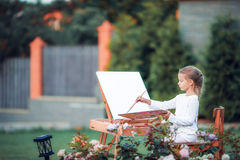 Adorable little girl painting a picture on an Royalty Free Stock Images
