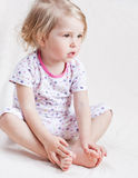 Adorable little girl in pajamas. Sitting holding hands on their feet on a white background stock image
