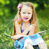 Adorable little girl with pencils and note in a park Royalty Free Stock Photos