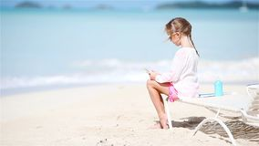 Little girl making video or photo with by her camera sitting on the sunbed stock video footage