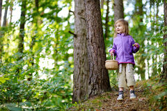 Adorable little girl picking berries in the forest. On summer day Stock Photo