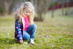 Adorable little girl picking the first flowers of spring on beautiful spring day. Cute child having fun outdoors Royalty Free Stock Image