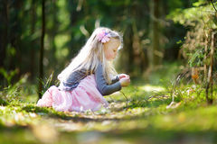 Adorable little girl picking the first flowers of spring in the woods on beautiful sunny spring day. Cute child having fun outdoors royalty free stock photos