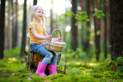 Adorable little girl picking foxberries in the forest stock photo
