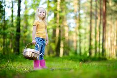 Adorable little girl picking foxberries in the forest Stock Photos