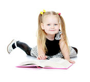 Adorable little girl with pigtails reading a book Stock Photo
