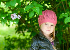 Adorable little girl in pink hat smiling in a park Royalty Free Stock Photos