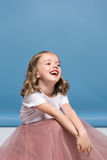 Adorable little girl in pink skirt sitting on floor and laughing Stock Images