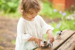 Adorable little girl play with animal toys. Cute toddler girl playing with farm animal figures outdoors. Summer leisure. childhood on countryside. Child Royalty Free Stock Photography