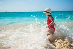 Adorable little girl play with water at beach during caribbean vacation Royalty Free Stock Photography