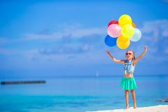 Adorable little girl playing with balloons at the Stock Photos
