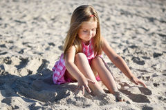 Adorable little girl playing on beach. With a sand Royalty Free Stock Photo
