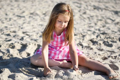 Adorable little girl playing on beach. In summer Stock Images