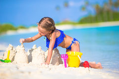 Adorable little girl playing with beach toys. During summer vacation Stock Photos