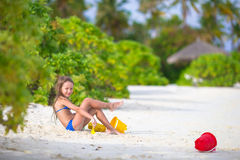 Adorable little girl playing with beach toys. Little girl playing with beach toys during tropical vacation Stock Photos