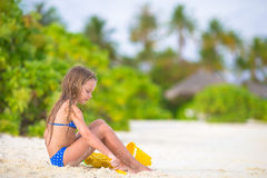 Adorable little girl playing with beach toys. Little girl playing with beach toys during tropical vacation Royalty Free Stock Photos