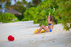 Adorable little girl playing with beach toys. Little girl playing with beach toys during tropical vacation Stock Photo