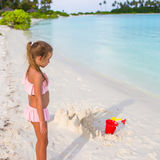 Adorable little girl playing with beach toys during tropical vacation. Adorable little girl playing with beach toys during summer vacation Stock Image