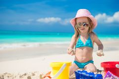 Adorable little girl playing with beach toys. Adorable girl playing on the beach with white sand Royalty Free Stock Photo