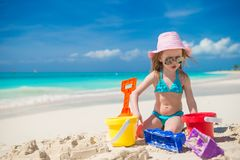 Adorable little girl playing with beach toys. Adorable girl playing on the beach with white sand Royalty Free Stock Image