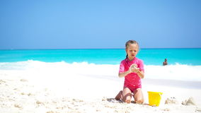 Adorable little girl playing with beach toys on white sandy beach stock footage