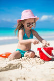 Adorable little girl playing on the beach with white sand Stock Images