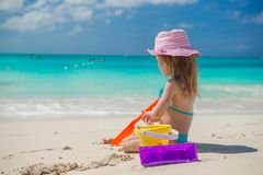 Adorable little girl playing on beach with white. Adorable little girl playing on the beach with white sand Stock Photos