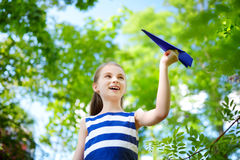 Adorable little girl playing with blue paper plane outdoors Royalty Free Stock Photo