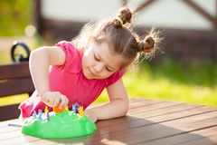 Adorable little girl playing board game outdoors stock photo