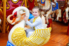 Adorable little girl playing on carousel at amusement park Royalty Free Stock Photos