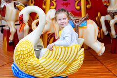 Adorable little girl playing on carousel at amusement park. At summer Royalty Free Stock Image