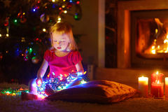 Adorable little girl playing with Christmas lights Royalty Free Stock Photos