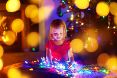 Adorable little girl playing with Christmas lights Stock Images