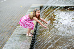 Adorable little girl playing with a city fountain on hot and sunny summer day. Adorable little girl playing with a city fountain Royalty Free Stock Image