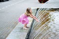 Adorable little girl playing with a city fountain on hot and sunny summer day. Adorable little girl playing with a city fountain on hot summer day Stock Image