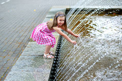 Adorable little girl playing with a city fountain on hot and sunny summer day. Adorable little girl playing with a city fountain on sunny summer day Royalty Free Stock Photos