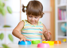 Adorable little girl playing with cup toys, smiling. Royalty Free Stock Photos