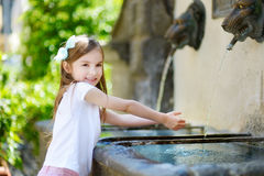 Adorable little girl playing with a drinking water fountain Stock Photography