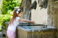 Adorable little girl playing with a drinking water fountain Stock Photo