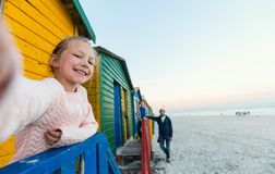 Little girl at Muizenberg beach. Adorable little girl playing at famous colorful huts of Muizenberg beach near Cape Town in South Africa Stock Images