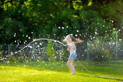 Adorable little girl playing with a garden hose. On hot and sunny summer evening royalty free stock photo