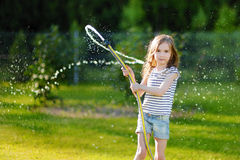 Adorable little girl playing with a garden hose Royalty Free Stock Photography