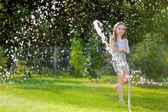 Adorable little girl playing with a garden hose Stock Photo