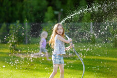 Adorable little girl playing with a garden hose Royalty Free Stock Photos