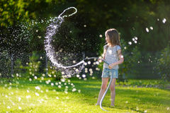 Adorable little girl playing with a garden hose Royalty Free Stock Images
