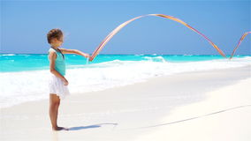 Adorable little girl playing with gymnastic ribbon on the beach. Slow motion stock video footage