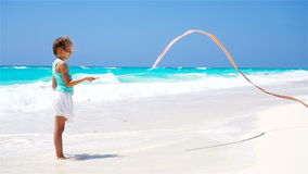 Adorable little girl playing with gymnastic ribbon on the beach. SLOW MOTION stock video